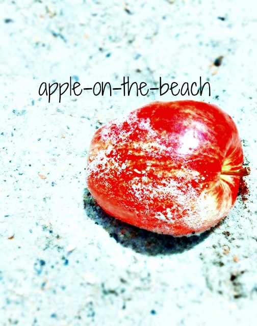 Red apple in the sand at the beach